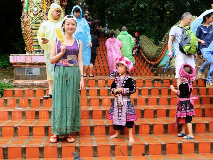 很多当地小朋友穿着民族服装在楼梯上给游客拍合照赚钱.