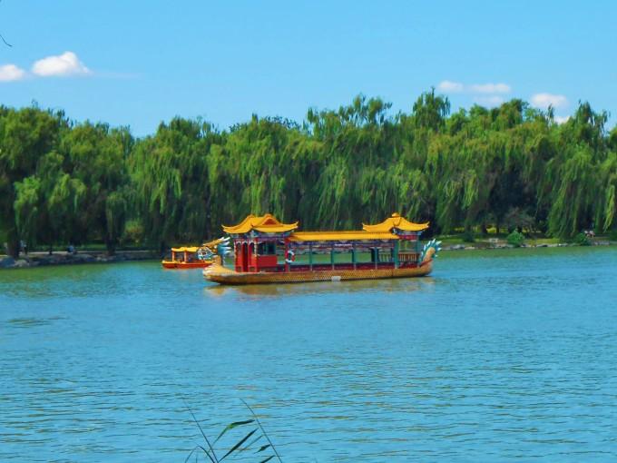 """初秋的北京酷熱依然,一場大雨帶來了難得的涼爽。雨紛紛揚揚持續了一整天,給北京市民的出行帶來不便。   八月十九日,雨後第二天的清晨,天空放晴,陽光普照。約好友到頤和園西堤晨運,走圈子。乘地鐵四號線到北宮門,入園,沿著蘇州河奔西堤而行。   雨後的西堤生機昂然,千頃昆明湖碧波蕩漾,岸邊的垂柳蔥綠,修長的枝葉輕拂水面,迎風飄逸。南湖的荷花開得正旺。翠綠荷田一望無邊,星星點點的荷花點綴其中嬌豔粉紅。遊船畫舫穿梭於濃密荷田之中,好一幅湖中荷花堤邊柳,碧波輕搖蕩綠舟""""的秀美山水畫卷。   漫步到耕織圖景區,靜觀"""